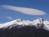 "A seemingly motionless ""flag"" of cloud above the mountains."